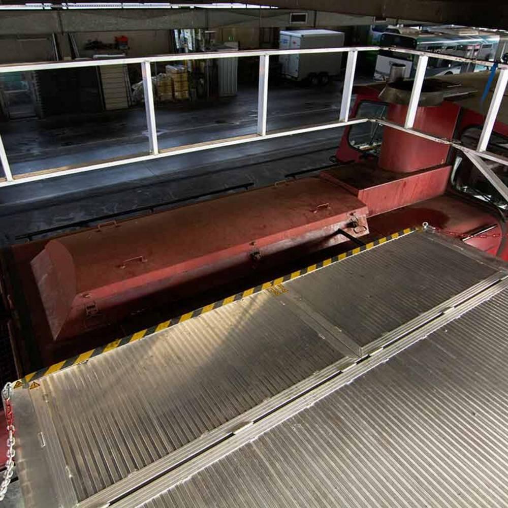 Fahrbare Arbeitsbühne mit ausgefahrenen Auskragungen und ausgeklapptem Geländer